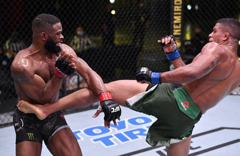 Gilbert Burns of Brazil kicks Tyron Woodley in their welterweight fight