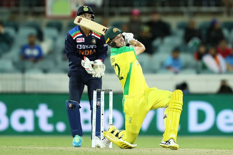 Cameron Green plays a lofted shot as KL Rahul looks on from behind the stumps
