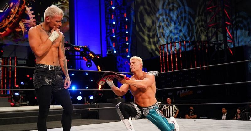 Cody Rhodes handing over the TNT Championship to Darby Allin at AEW Full Gear.