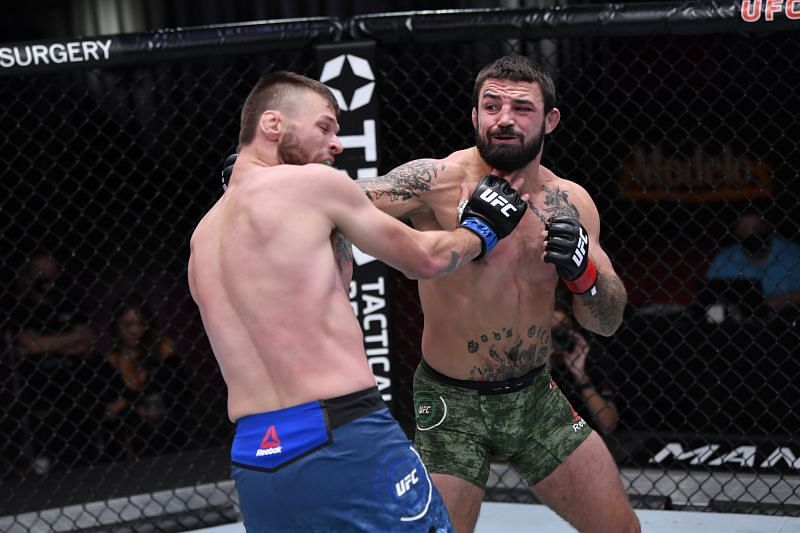 Mike Perry punches Tim Means in their welterweight bout