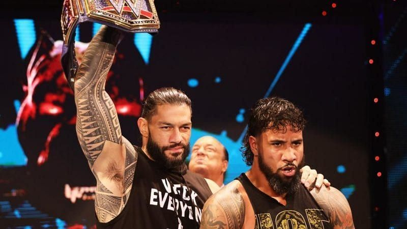 Roman Reigns and Jey Uso with Paul Heyman in the background