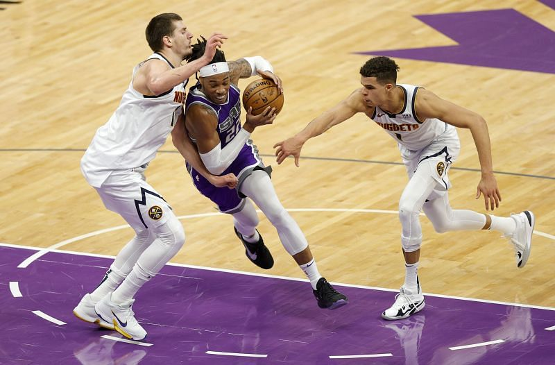 Richaun Holmes is guarded by Nikola Jokic and Michael Porter Jr. of the Denver Nuggets