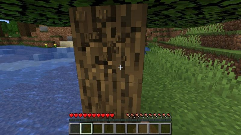 Punching a tree for a wood log in Minecraft. (Image via Minecraft)