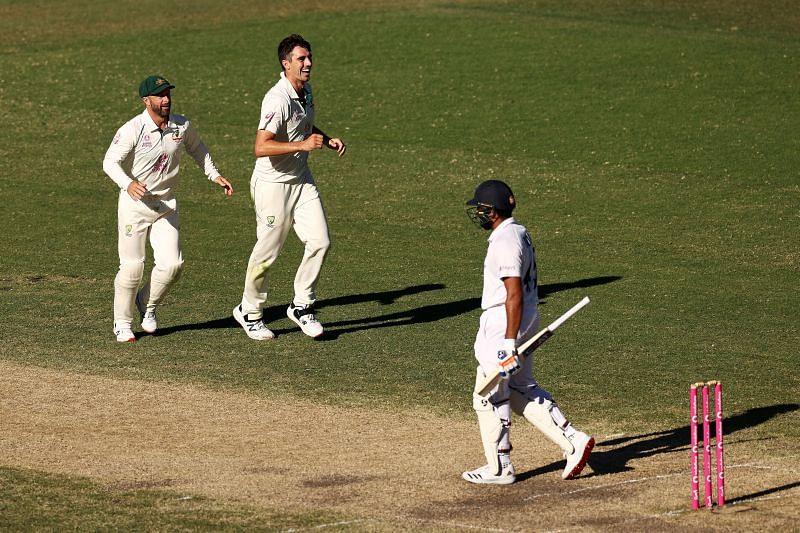 Pat Cummins celebrates after dismissing Rohit Sharma.