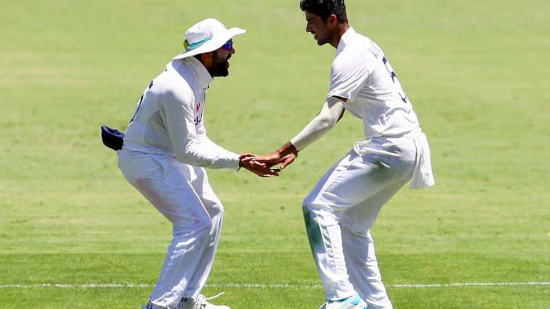 Washington Sundar celebrates with Rohit Sharma after dismissing Steve Smith for his first Test wicket