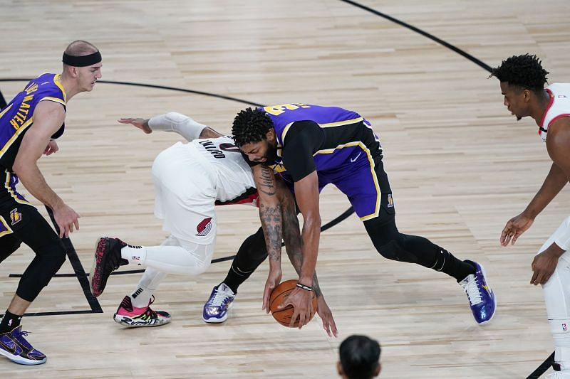 Anthony Davis #3 of the Los Angeles Lakers and Damian Lillard #0 of the Portland Trail Blazers scramble for a loose ball (Photo by Ashley Landis-Pool/Getty Images)