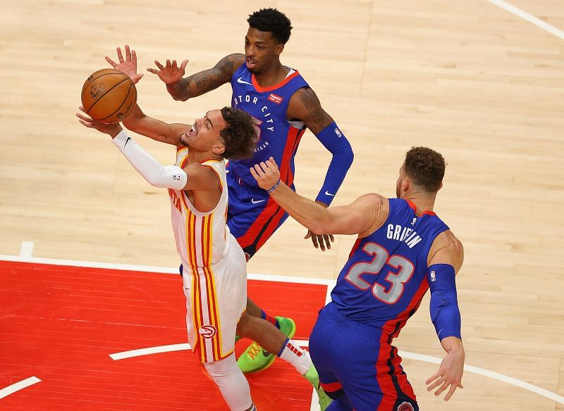 Trae Young #11 of the Atlanta Hawks draws a foul as he drives between Delon Wright #55 and Blake Griffin #23 of the Detroit Pistons during the first half at State Farm Arena on January 20, 2021 in Atlanta, Georgia. (Photo by Kevin C. Cox/Getty Images)