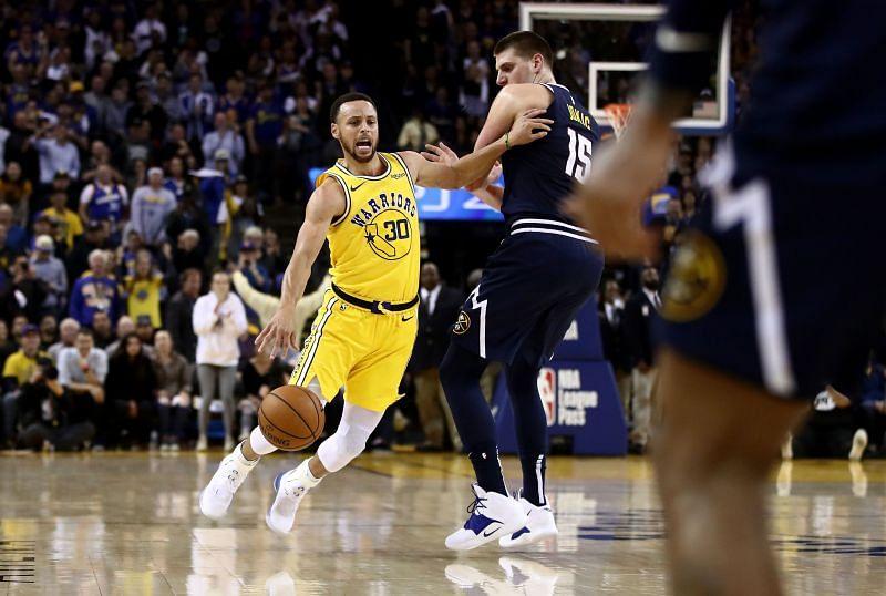 Stephen Curry dribbles past Nikola Jokic.