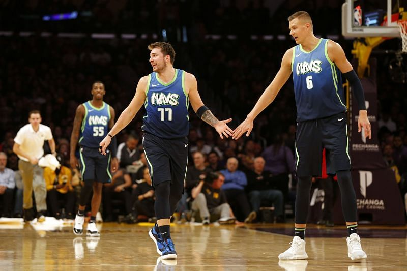 Luka Doncic and Kristaps Porzingis of the Dallas Mavericks high-five during a game against the Los Angeles Lakers