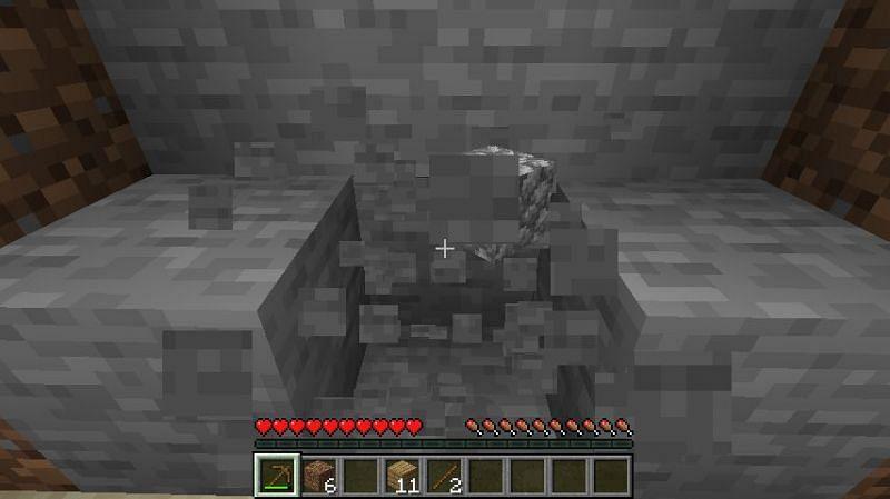 Mining stone blocks in Minecraft. (Image via Minecraft)