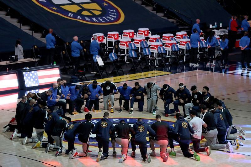 The Denver Nuggets and the DallasMavericks before the playing of the National Anthem