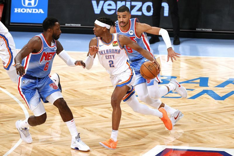 Shai Gilgeous-Alexander #2 of the Oklahoma City Thunder dribbles against Jeff Green #8 and Timothe Luwawu-Cabarrot #9 of the Brooklyn Nets