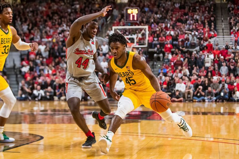 Davion Mitchell #45 of the Baylor Bears drives against Chris Clarke #44 of the Texas Tech Red Raiders