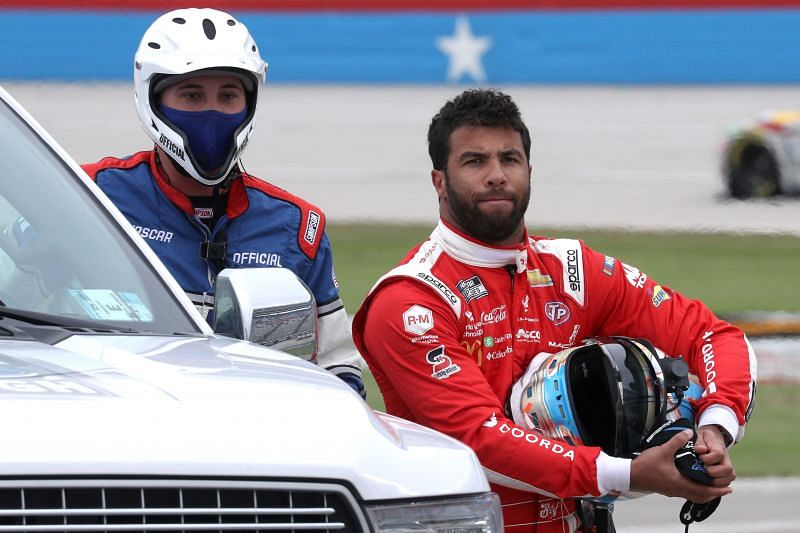 FORT WORTH, TEXAS - OCTOBER 28: Bubba Wallace, driver of the #43 Door Dash Chevrolet, walks off the track escorted by the NASCAR safety team after an on-track incident during the NASCAR Cup Series.