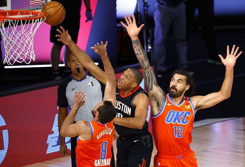 Eric Gordon of the Houston Rockets shoots against Danilo Gallinari and Steven Adams of the Oklahoma City Thunder