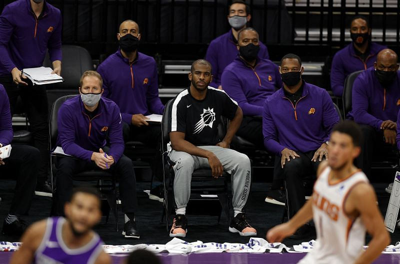 PChris Paul of the Phoenix Suns sits with the coaches on the bench during their game against the Sacramento Kings