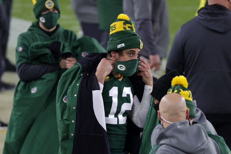 Aaron Rodgers puts on his Green Bay Packers themed face mask
