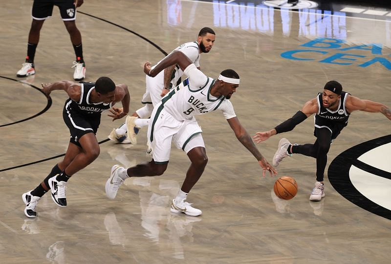 Bobby Portis #9 of the Milwaukee Bucks drives against Reggie Perry #0, and Bruce Brown #1 of the Brooklyn Nets.