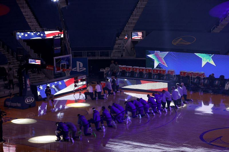 The Golden State Warriors take a knee for the national anthem.