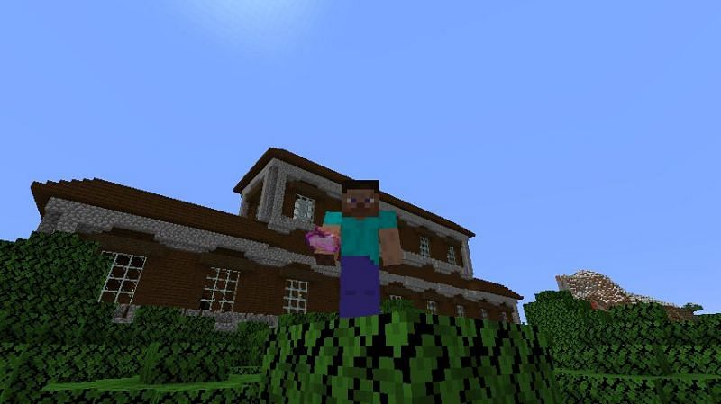 Steve holding an enchanted golden apple near a woodland mansion in Minecraft. (Image via Minecraft)