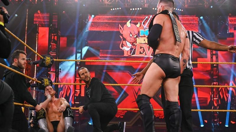 Finn Balor looks on as Undisputed Era consoles Kyle O