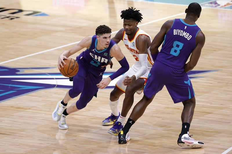 LaMelo Ball of the Charlotte Hornets drives to the basket against Cam Reddish.