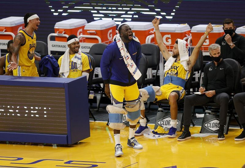 Damion Lee #1, Kent Bazemore #26, Draymond Green #23, and Stephen Curry #30 of the Golden State Warriors celebrate on the bench during the fourth quarter of their win over the Sacramento Kings