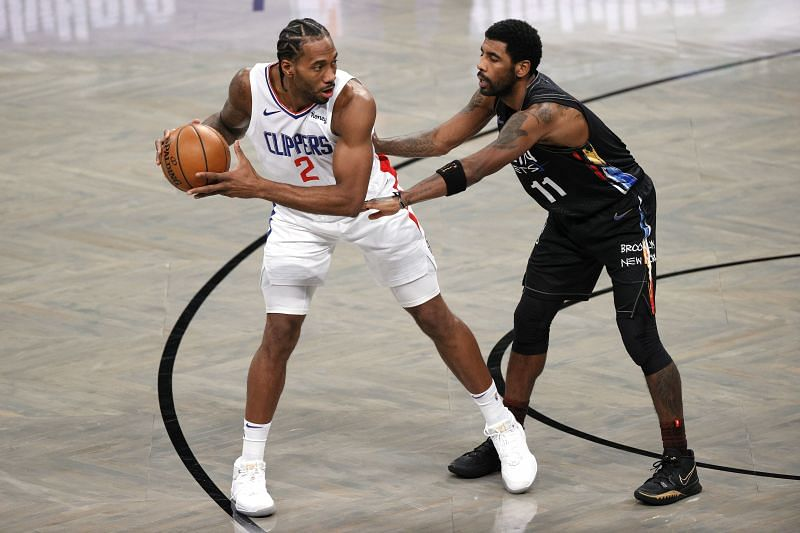 Kawhi Leonard #2 of the LA Clippers dribbles against Kyrie Irving #11 of the Brooklyn Nets.