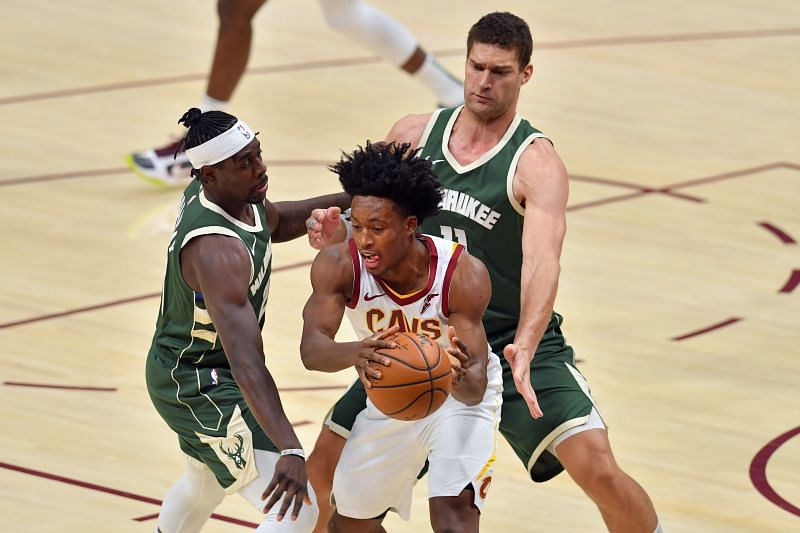 Collin Sexton of the Cleveland Cavaliers tries to pass under pressure from Jrue Holiday and Brook Lopez of the Milwaukee Bucks.