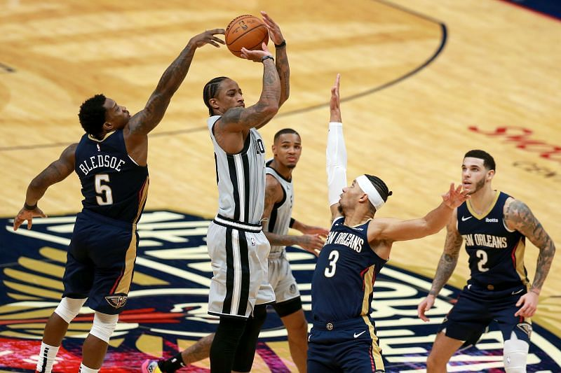 DeMar DeRozan (#10) of the San Antonio Spurs is blocked by Eric Bledsoe (#5) of the New Orleans Pelicans.