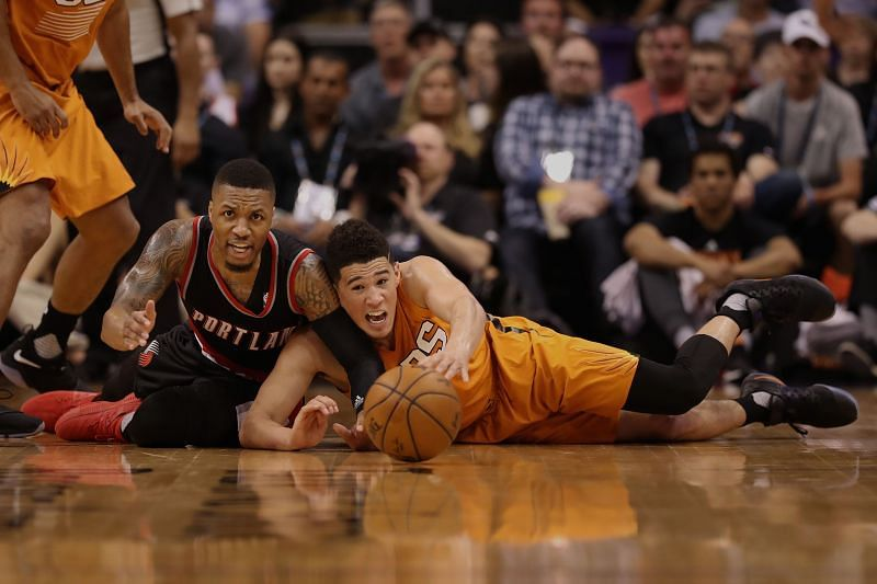 Damian Lillard #0 of the Portland Trail Blazers and Devin Booker #1 of the Phoenix Suns reach for a loose ball