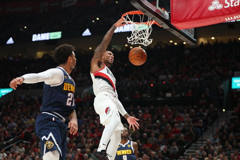 Damian Lillard #0 of the Portland Trail Blazers dunks the ball alongside Jamal Murray #27 of the Denver Nuggets in the first quarter during their season opener at Moda Center (Photo by Abbie Parr/Getty Images)