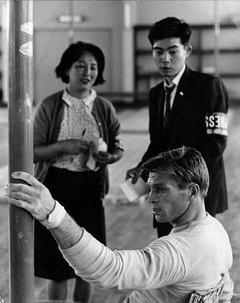 Two Japanese journalists watch champion Russian gymnast Boris Shakhlin training at Nippon University.