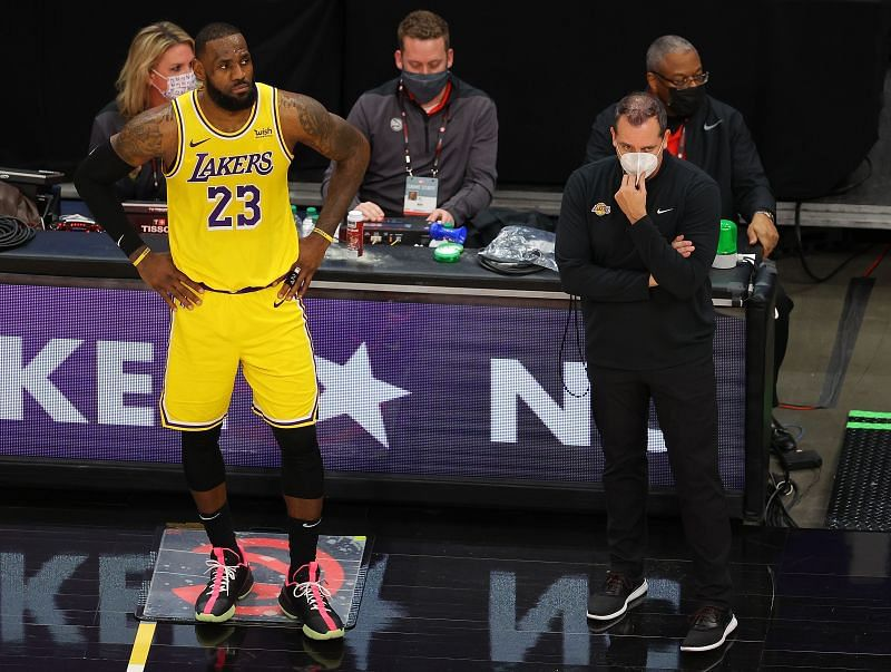 Head coach Frank Vogel of the Los Angeles Lakers stands with LeBron James #23.