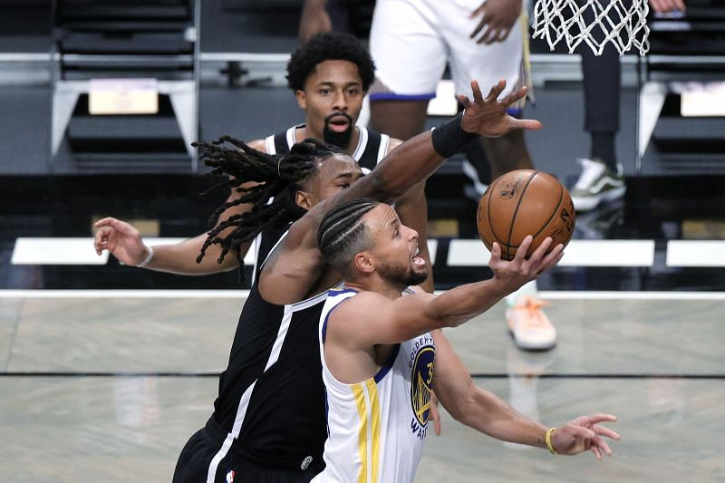 Stephen Curry of the Golden State Warriors attempts a layup against DeAndre Jordan and Spencer Dinwiddie of the Brooklyn Nets.