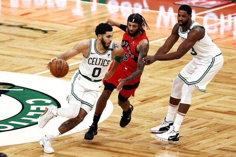 Jayson Tatum of the Boston Celtics dribbles down court past DeAndre