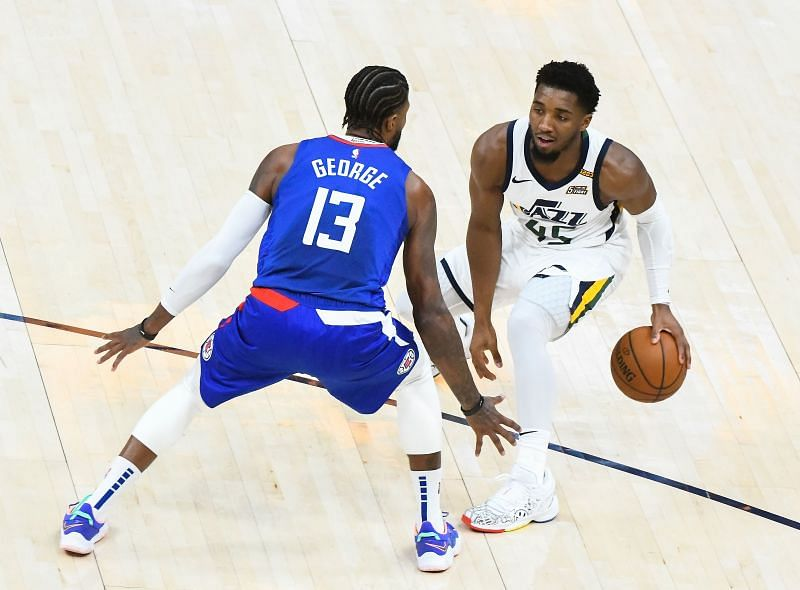 Donovan Mitchell #45 of the Utah Jazz looks to drive around Paul George #13 of the LA Clippers