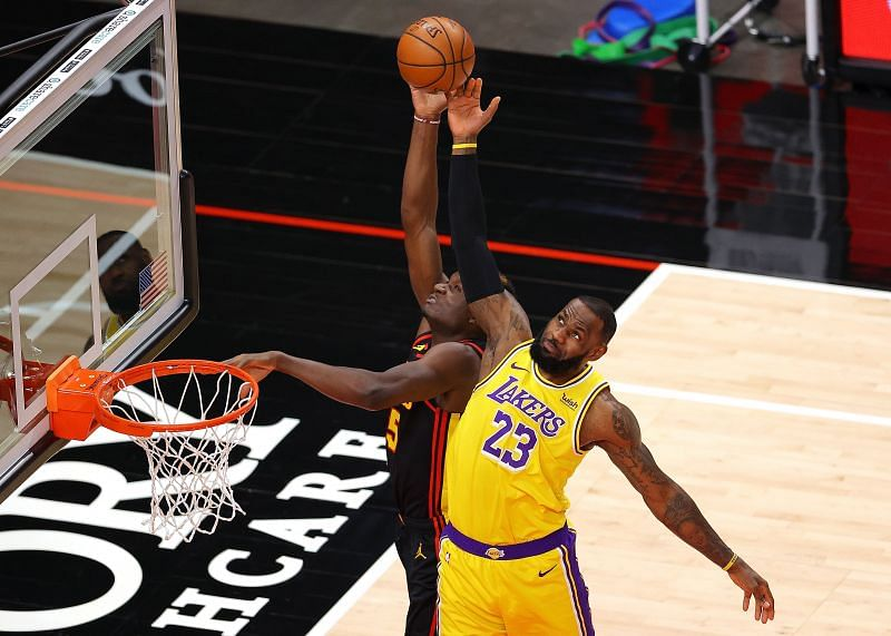 LeBron James #23 of the Los Angeles Lakers defends a pass intended for Clint Capela #15 of the Atlanta Hawks.