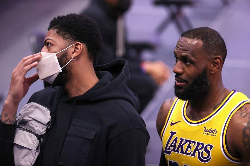 LeBron James #23 of the Los Angeles Lakers leaves the floor next to teammate Anthony Davis #3 who did not dress against the Detroit Pistons at Little Caesars Arena on January 28, 2021