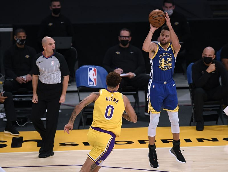 Stephen Curry #30 of the Golden State Warriors shoots a three-pointer in front of Kyle Kuzma #0 of the Los Angeles Lakers.