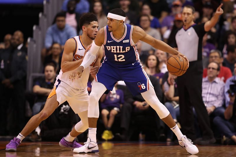 Tobias Harris of the Philadelphia 76ers goes up against Devin Booker of the Phoenix Suns