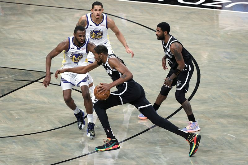Kevin Durant #7 of the Brooklyn Nets dribbles against Andrew Wiggins #22 of the Golden State Warriors