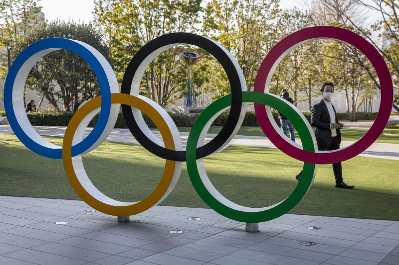 A man wearing a face mask walks past the Olympic Rings on February 11, 2021 in Tokyo, Japan.