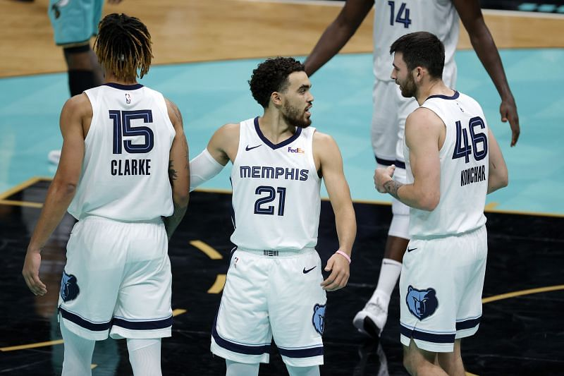 Tyus Jones #21 of the Memphis Grizzlies reacts with teammates Brandon Clarke #15 and John Konchar #46 during the fourth quarter of their game against the Charlotte Hornets at Spectrum Center (Photo by Jared C. Tilton/ Getty Images)