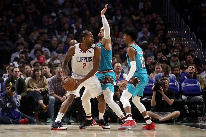 Kawhi Leonard #2 of the LA Clippers looks to pass the ball against Dillon Brooks #24 and Ja Morant #12 of the Memphis Grizzlies