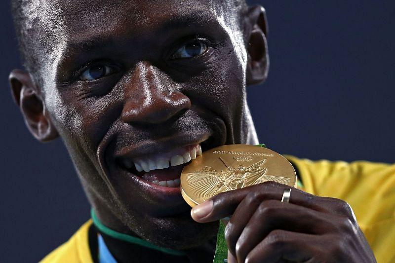 Usain Bolt biting his medal at the Olympics