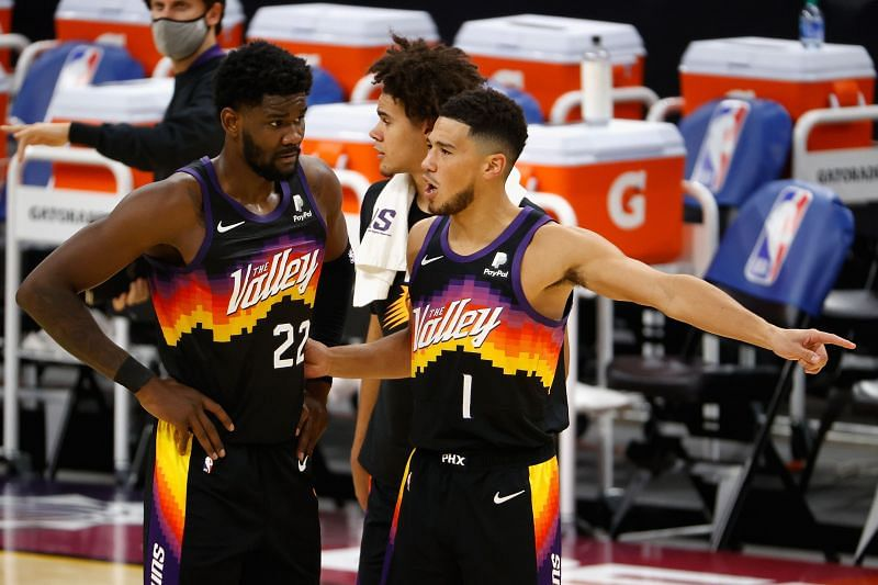 Devin Booker of the Phoenix Suns talks with Deandre Ayton.
