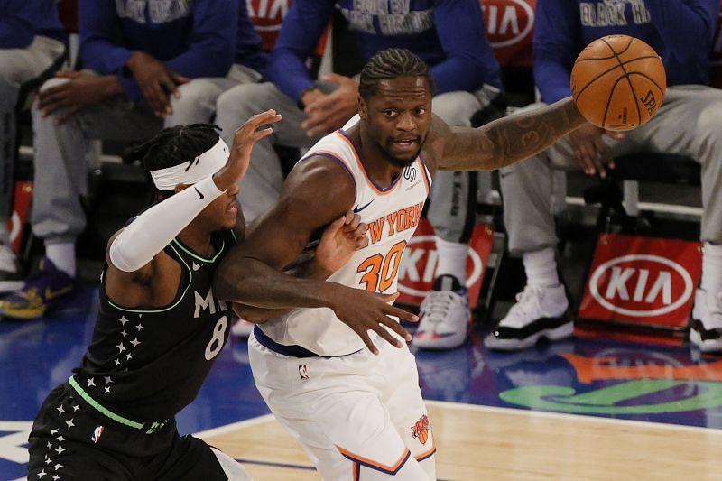 Julius Randle of the New York Knicks dribbles against Jarred Vanderbilt of the Minnesota Timberwolves