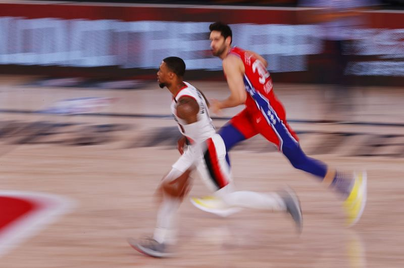 Damian Lillard #0 of the Portland Trail Blazers runs down the court against Furkan Korkmaz #30 of the Philadelphia 76ers