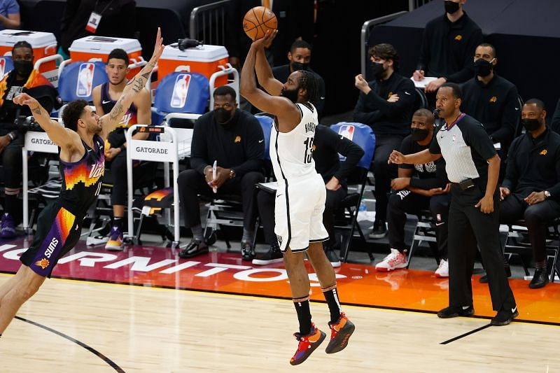 James Harden #13 of the Brooklyn Nets attempts a three-point shot over Abdel Nader #11 of the Phoenix Suns.